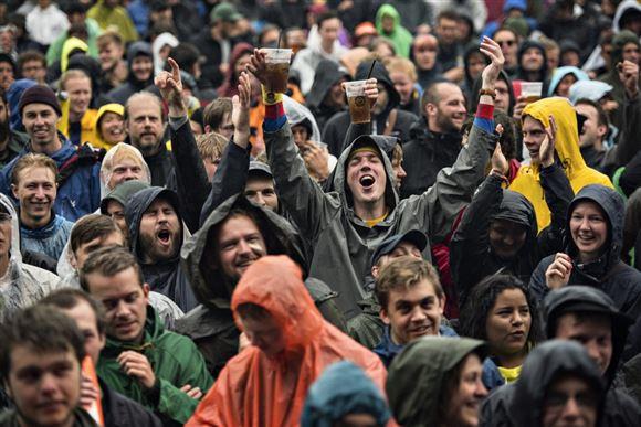 Mange festivalgængere skråler i regnvejr.