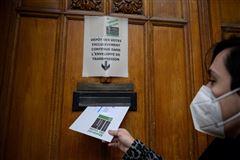 mand smider stemmeseddel i boks