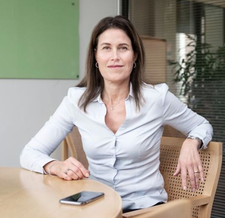 En kvinde ved et bord med en mobiltelefon smiler