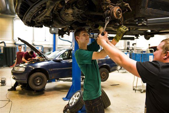 To unge reparerer en bil i en hal