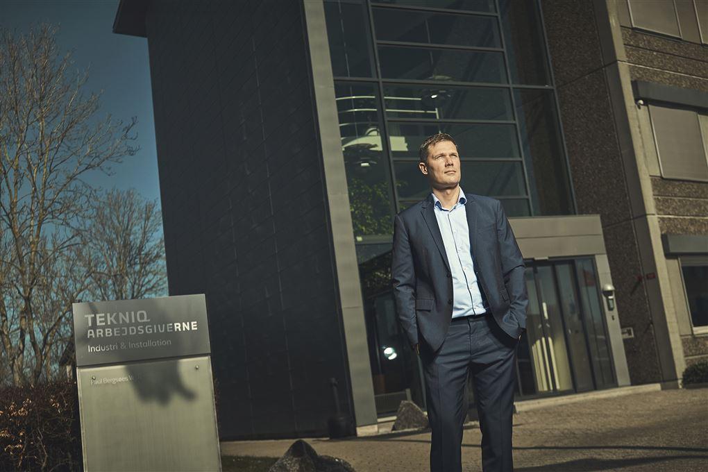 En mand i jakkesæt foran en bygning