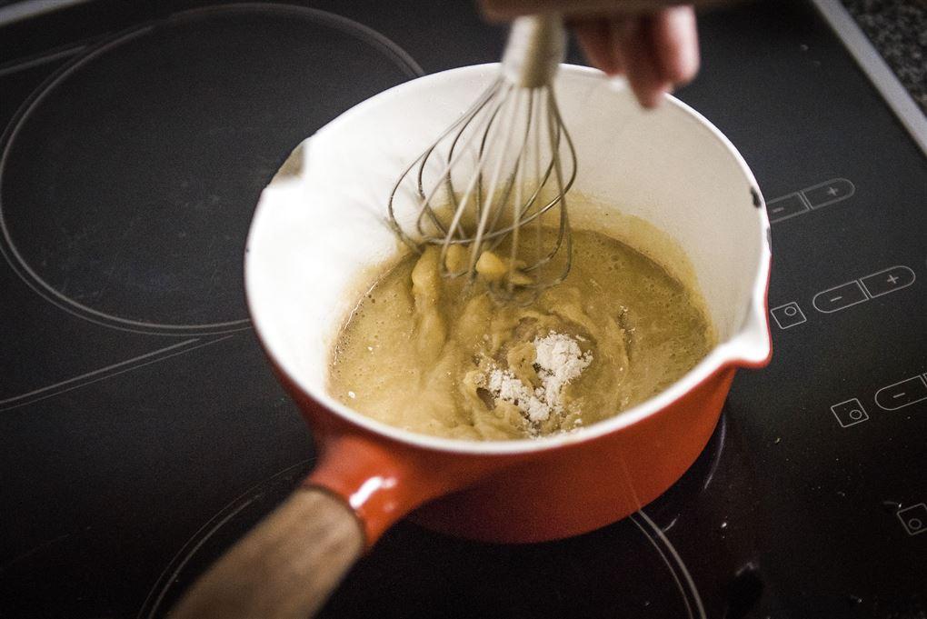 En lille kasserolle på et komfur det ligner begyndelsen på en opbagt sovs.