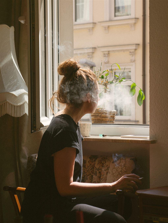 En kvinde sidder i en stue og ryger. Der er tåget omkring hende.