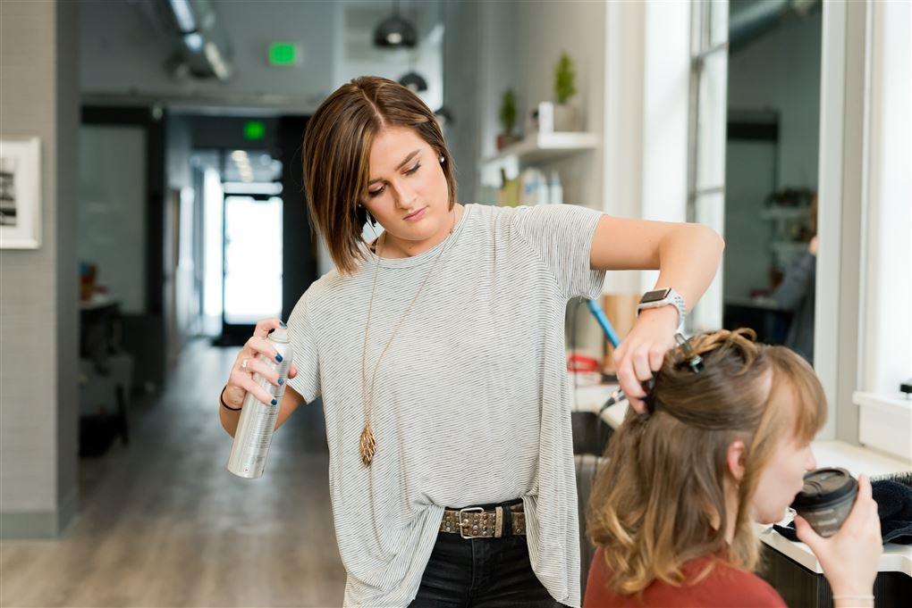 En frisør ornder hår i en salon