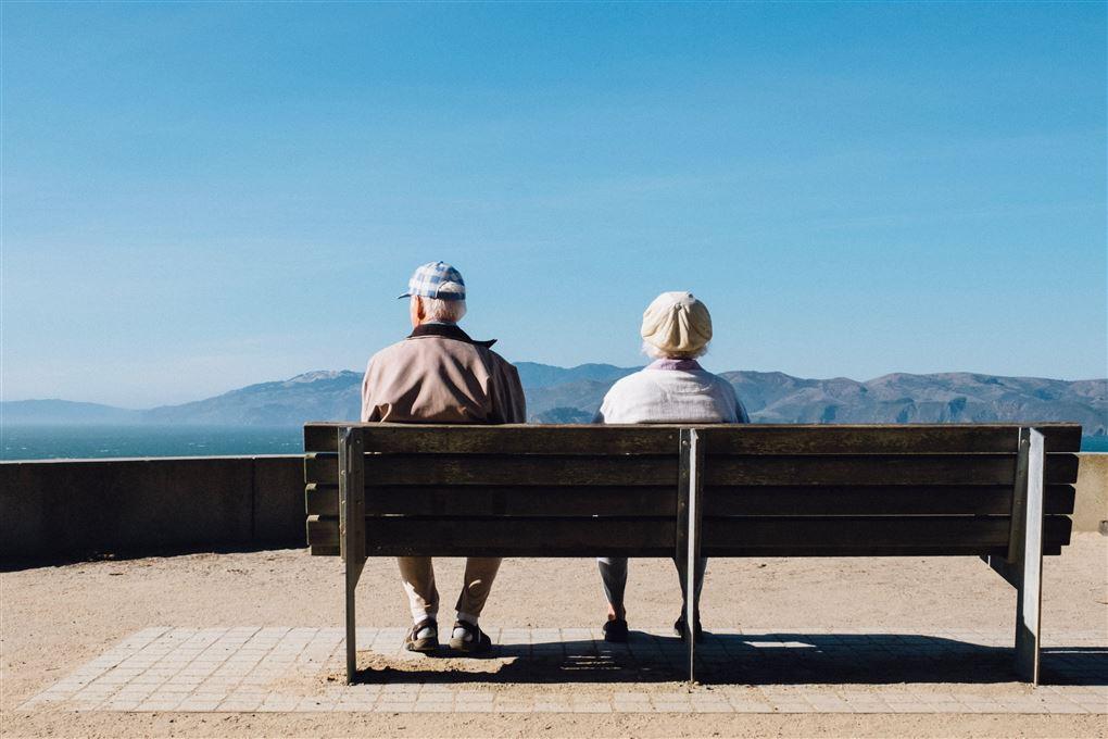 Et ældre par sidder på en bænk