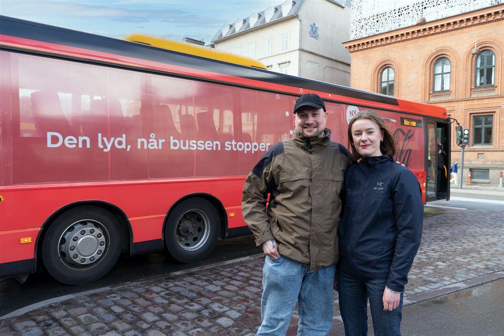 To unge mennesker ved en rød bus