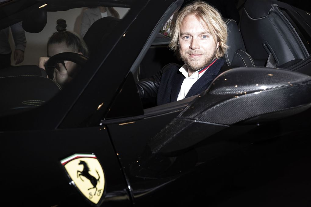tv-vært Felix Smith sidder bag rattet på en sort Ferrari.