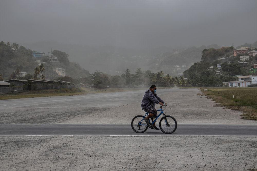 En cykelist kører igennem asken, der ligger over hele landskabet.