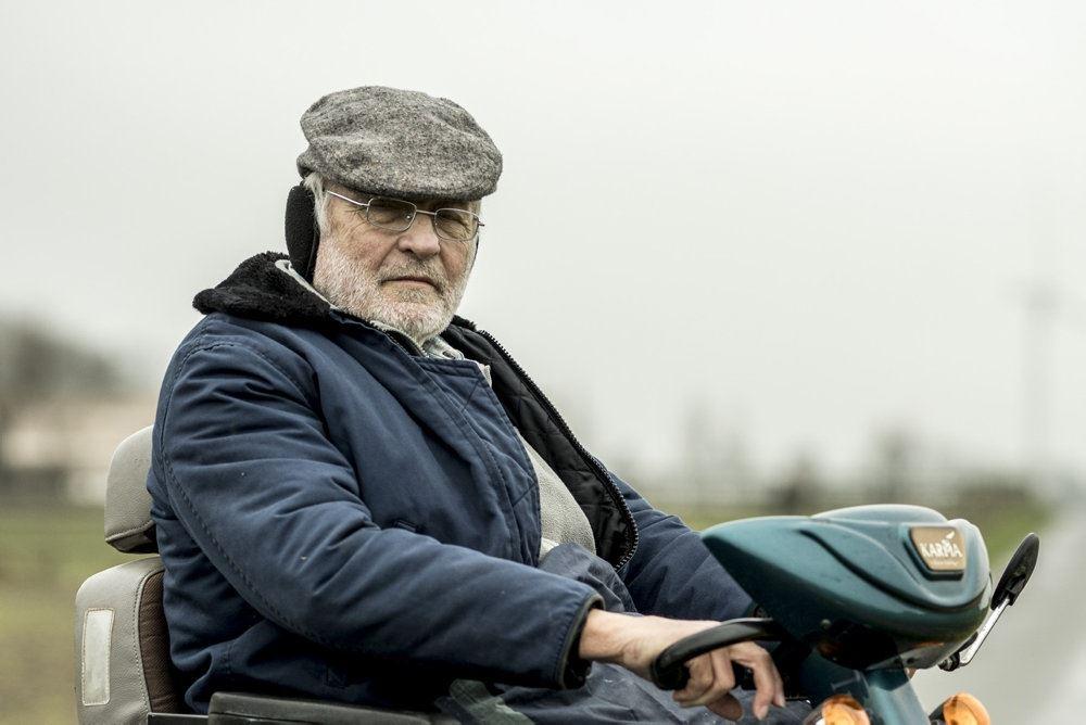 Niels Hausgaard med sixpence og gråt skæg. Han sidder på en bænk.