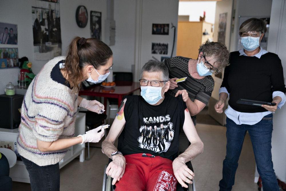 mand med mundbind bliver vaccineret med stik i skulderen