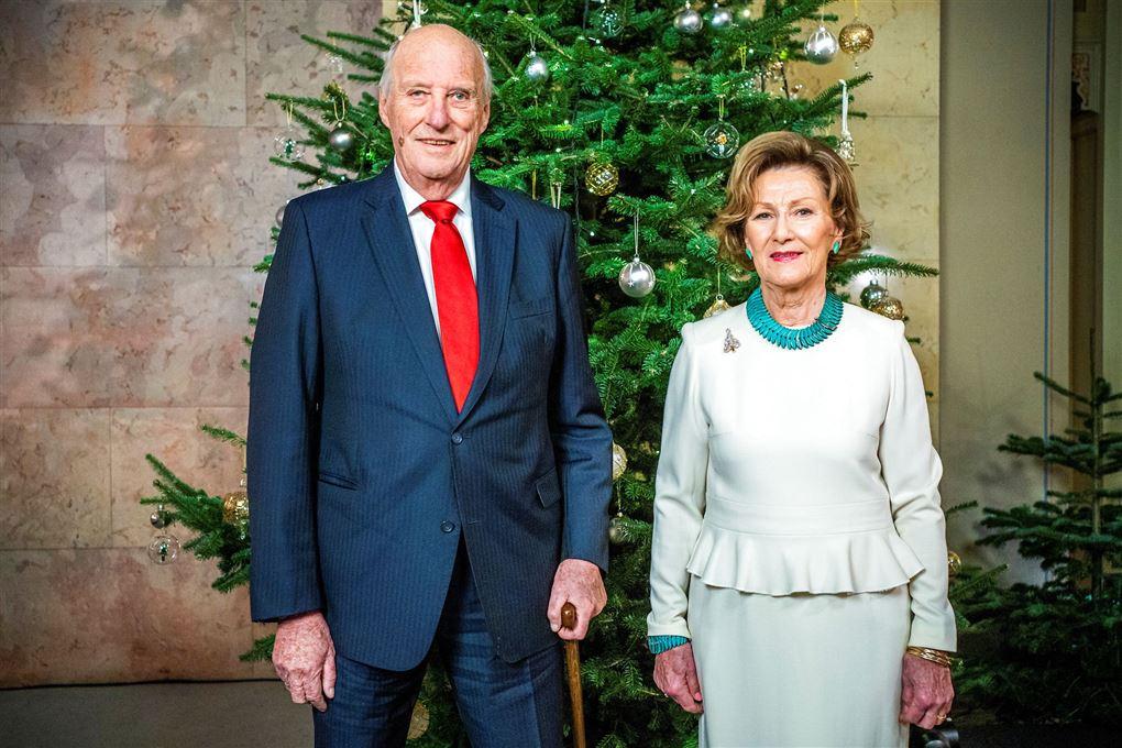 Kong Harald og Dronning Sonja står foran juletræ