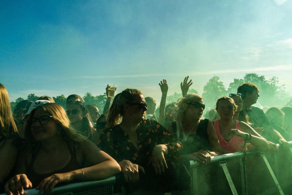 En stor flok glade mennesker til koncert i solskin.
