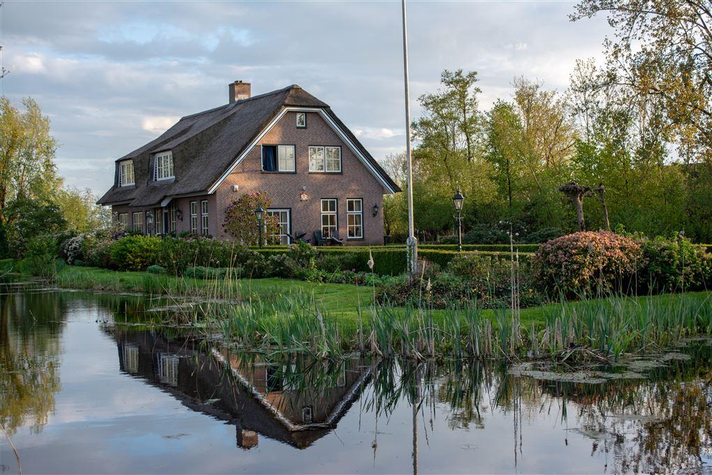 Et stort idyllisk hus med flagstang og sø i baghaven.