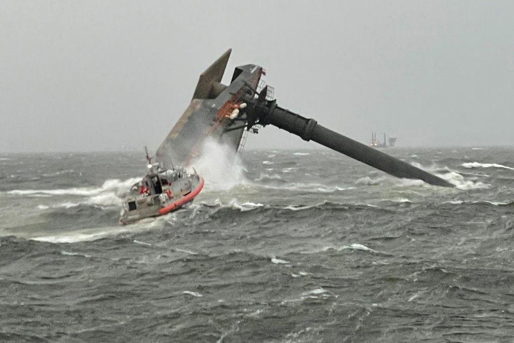 En kæntret båd og en gummibåd på vej mod den