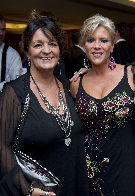 To kvinder i sorte kjoler smiler
