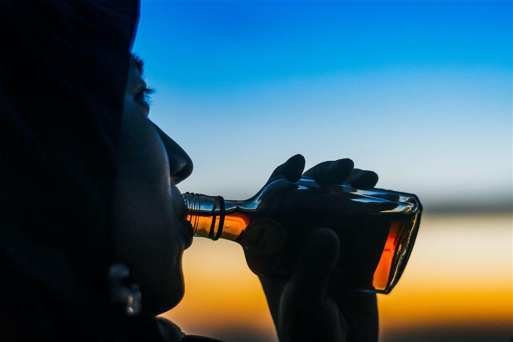 En person drikker direkte ud fra en flaske