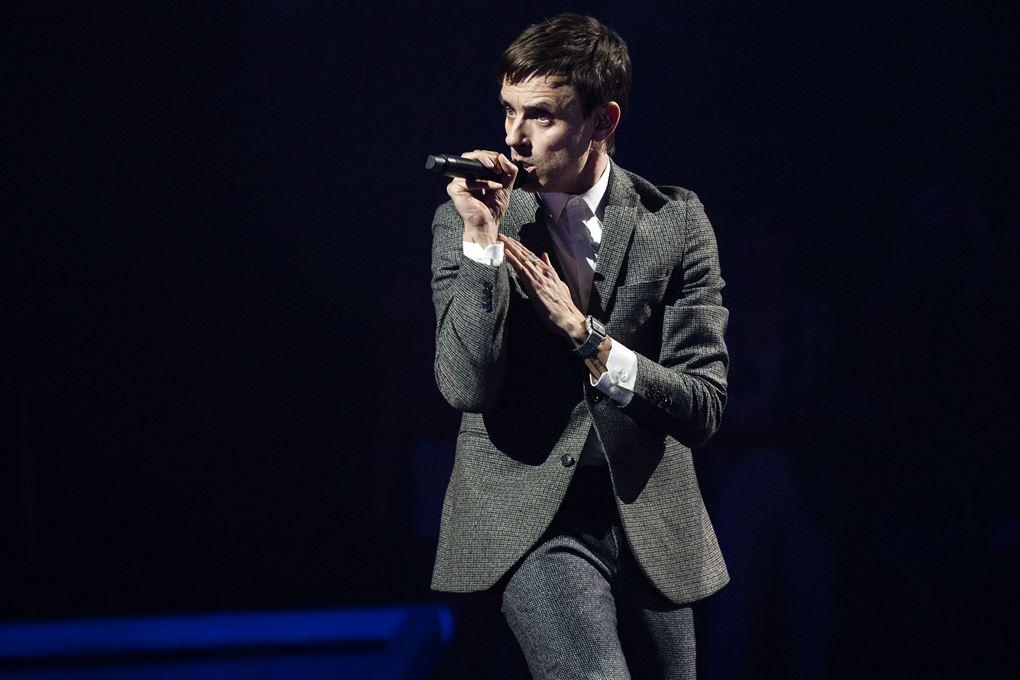 Simon Kvamm på scenen i X Factor han er i gråt jakkesæt.