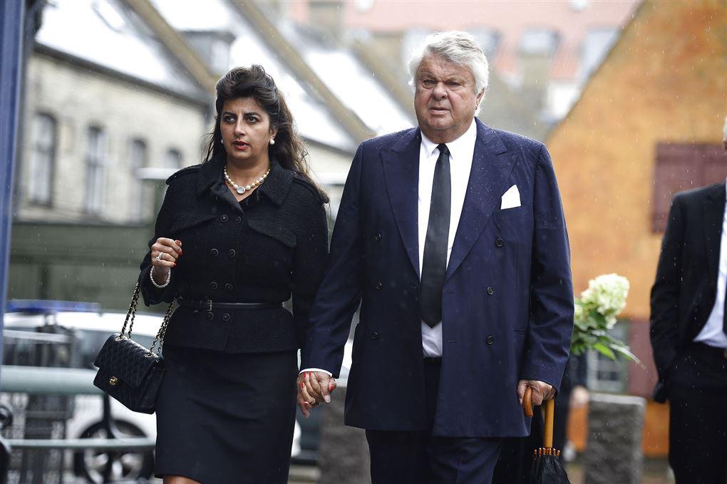 Susan Astani og Christian Kjær hånd i hånd klædt i sort med alvorlige miner.