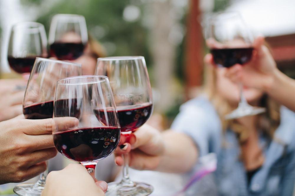 folk sidder udendørs og skåler med rødvin i glassene