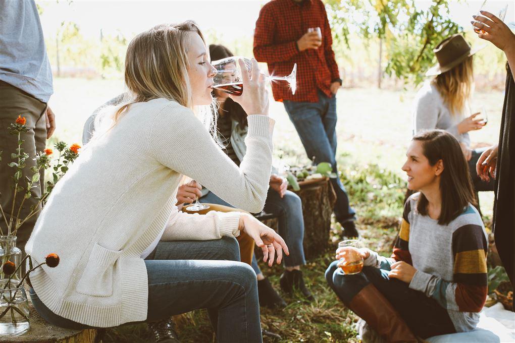Unge sidder udenfor og drikker vin