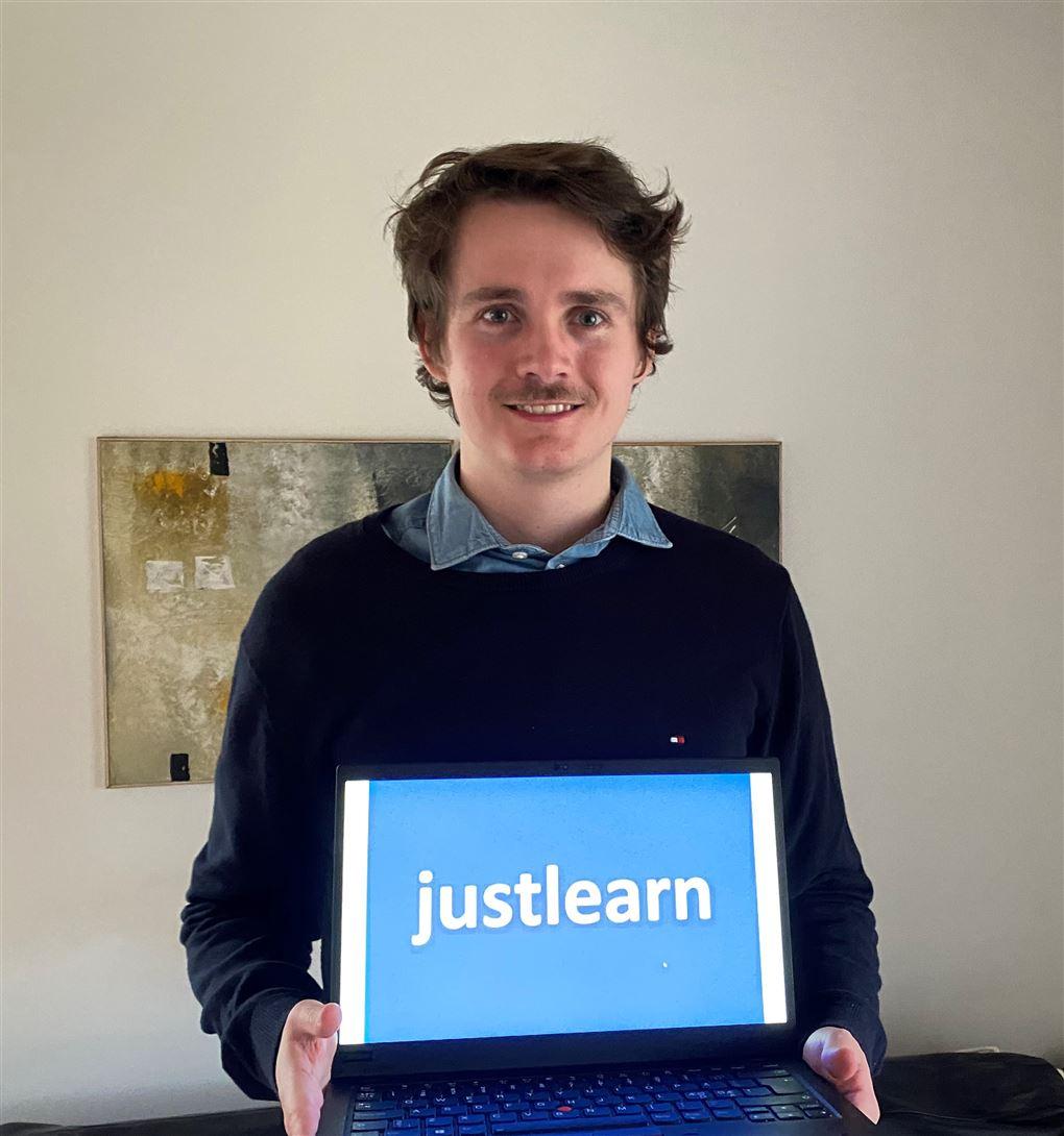 En smilende unge mand med en computer foran sig