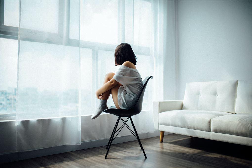 En kvinde kigger ud af et vindue med ryggen til