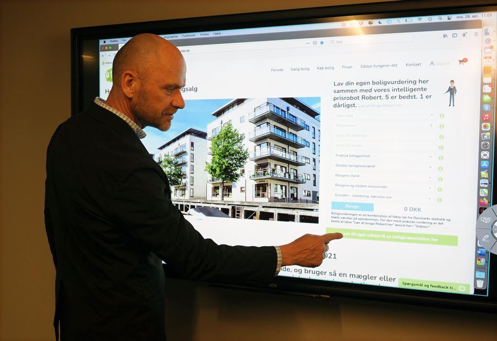 En mand peger på en bygning på en skærm
