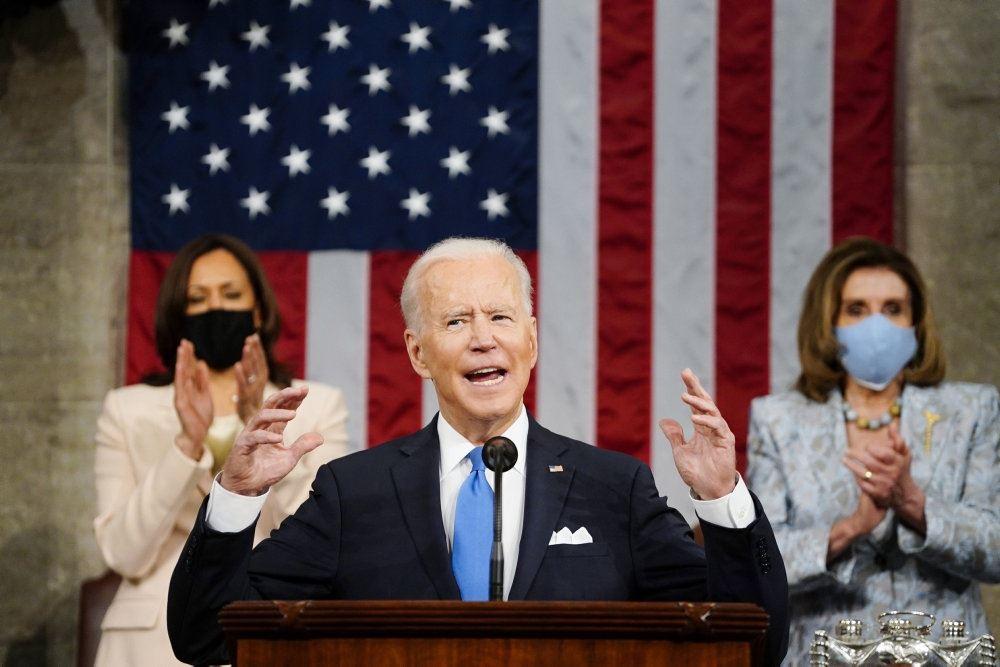 Biden taler med to kvinder i baggrunden og det amerikanske flag hængnede ned