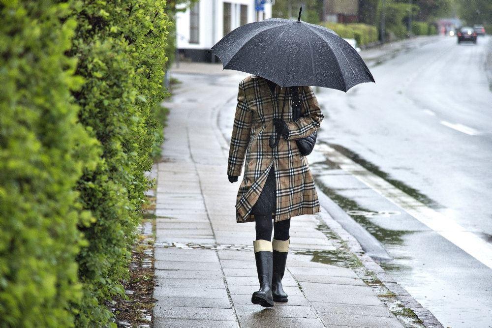 kvinde går i regnvejr med paraply