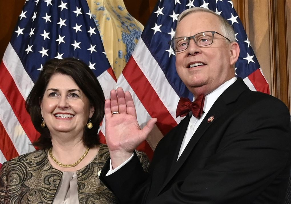en kvinde og en mand står foran amerikanske flag