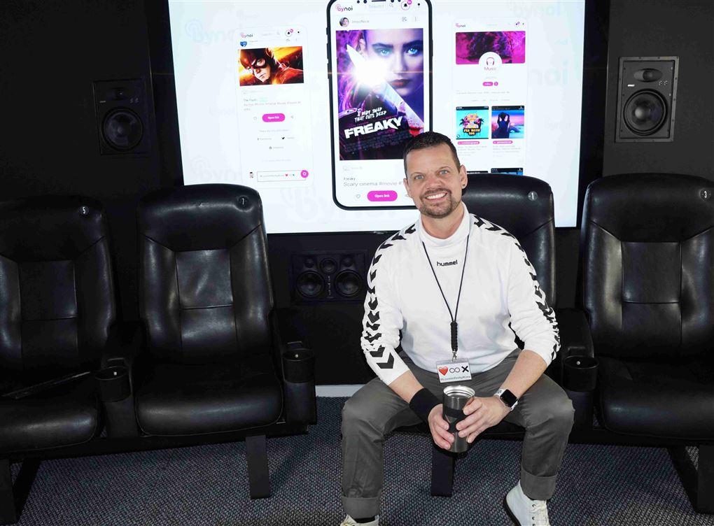 En smilende mand foran en kæmpe skærm