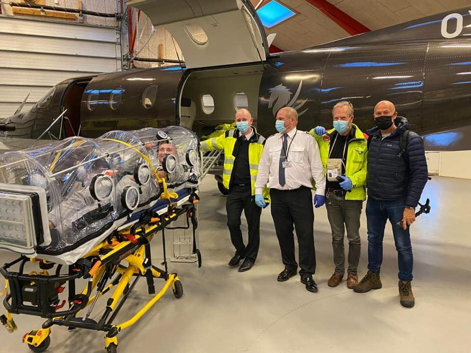 """Victor Axelsen ligger på en bårer i en gennemsigtig oppustet """"kapsel"""" der ligner en kuvøse. Bag ham står et mindre privatfly og fire mænd med handsker og masker."""