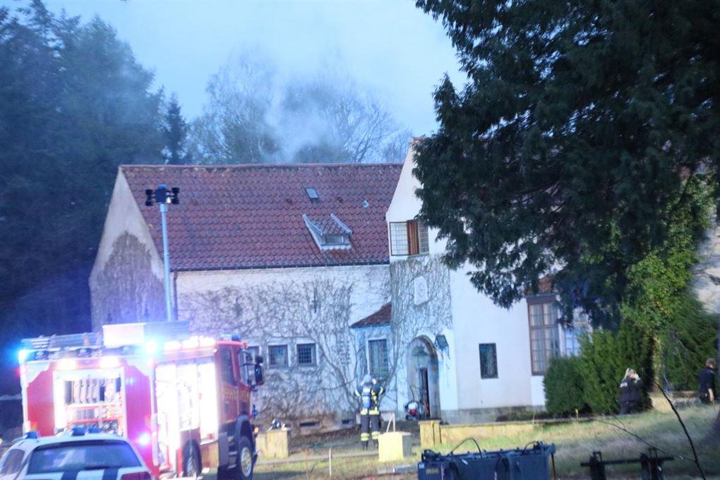 Villaen med røg fra taget og brandbiler udenfor.
