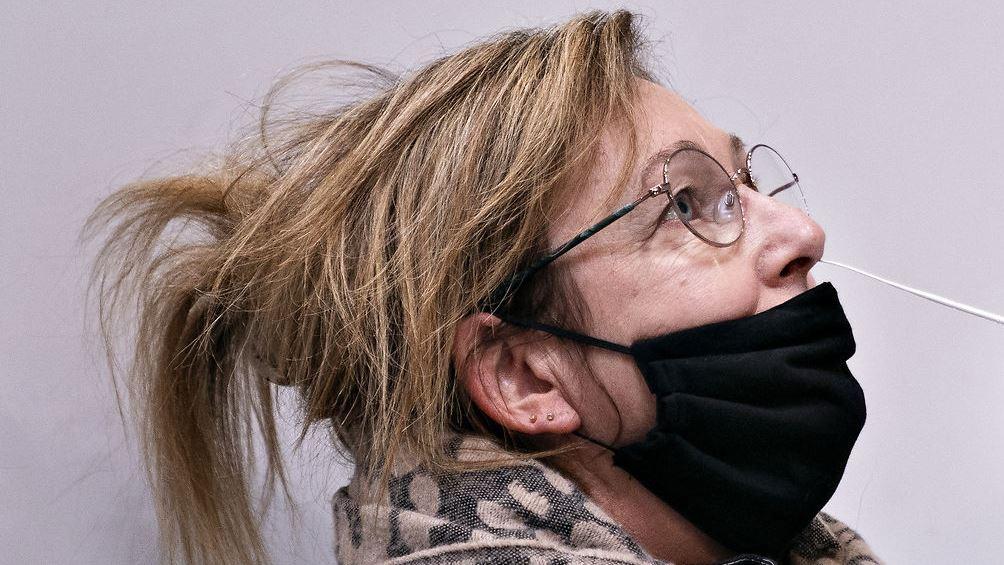 En kvinde med mundbind over munden og en vatpind i næsen.