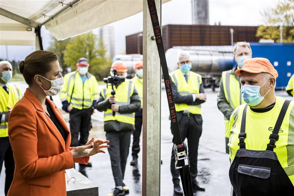 Mette F snakker med arbejdere i gult tøj