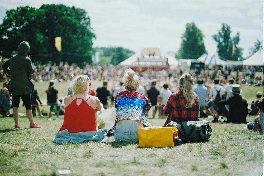 folk sidder på græsset til festival