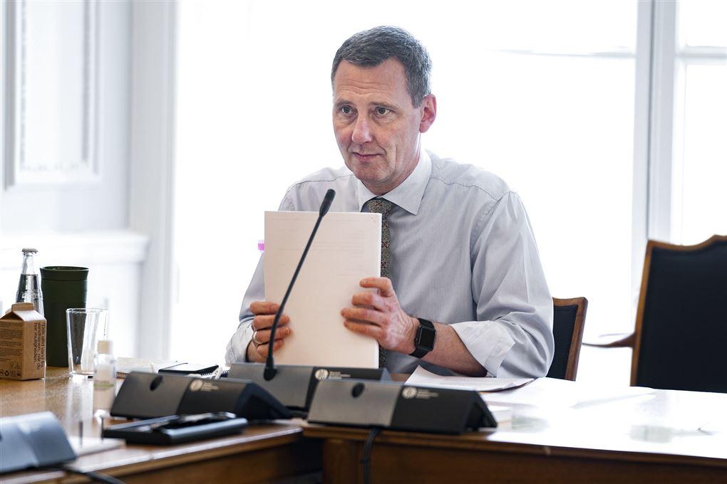 Nick Hækkerup sidder ved et bord med en bordmikrofon foran sig og en stor stak papirer i hånden.