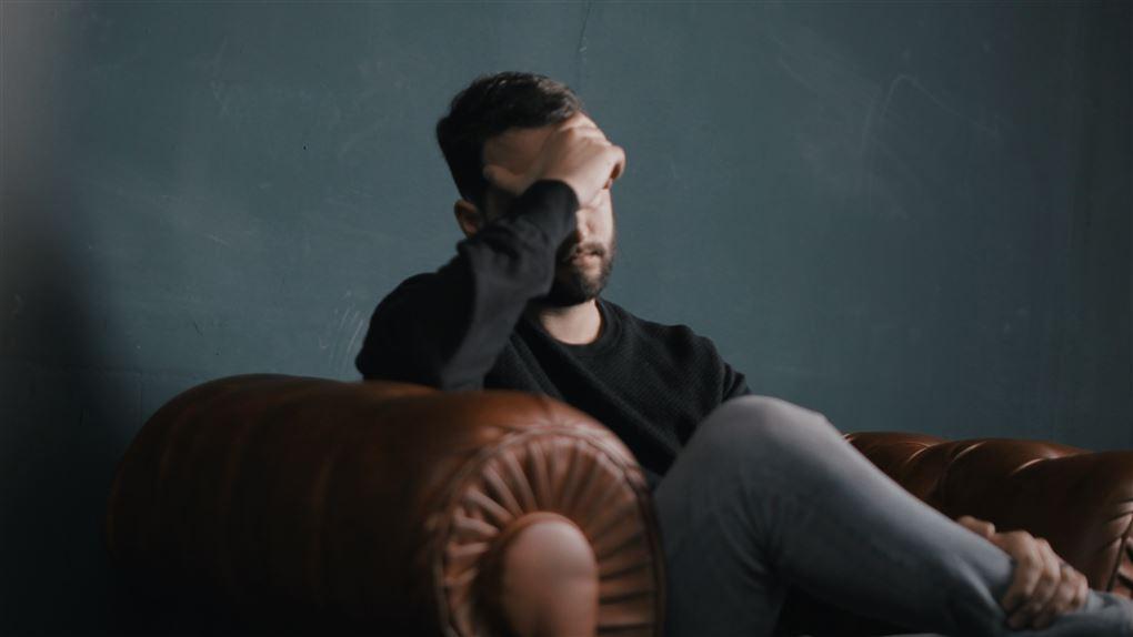 mand sidder i sofa og ser ærgerlig ud
