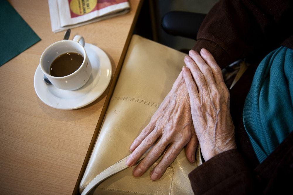 person sidder ved bord med en kop kaffe
