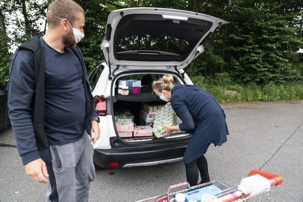 to personer står ved bil med åbent bagagerum