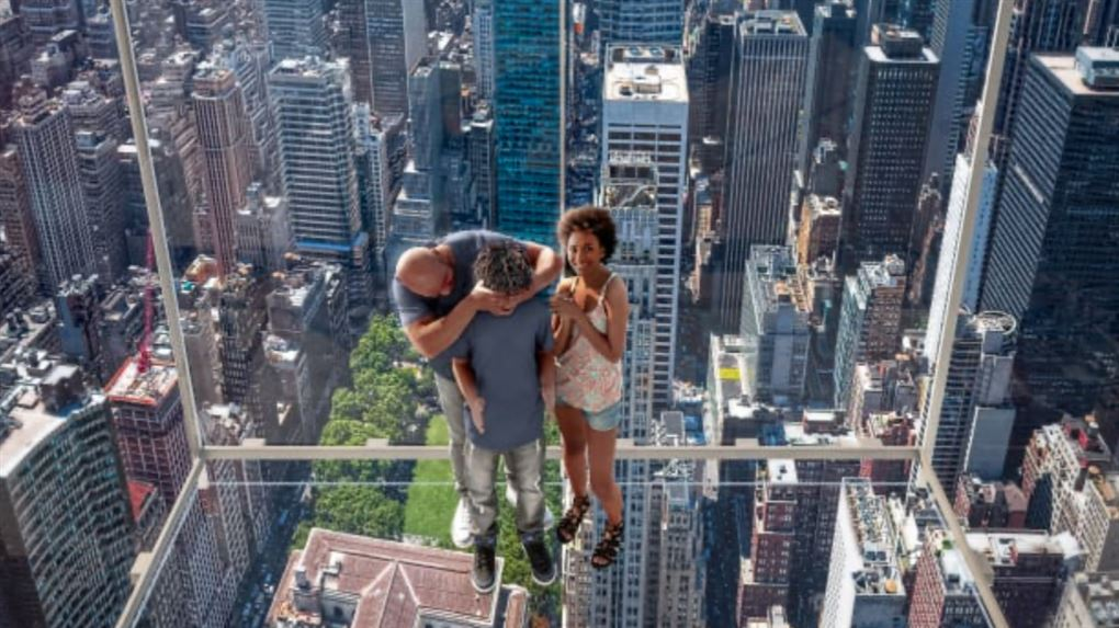 En far med sine to børn på et glasgulv over New Yorks gader