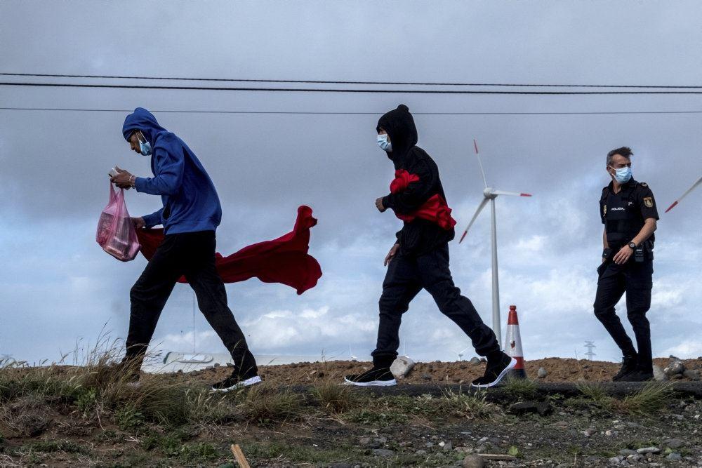 Migranter løber på en strand