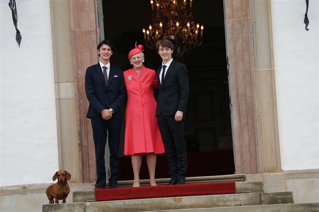 Margrethe i rødt med sine to børnebørn i jakkesæt