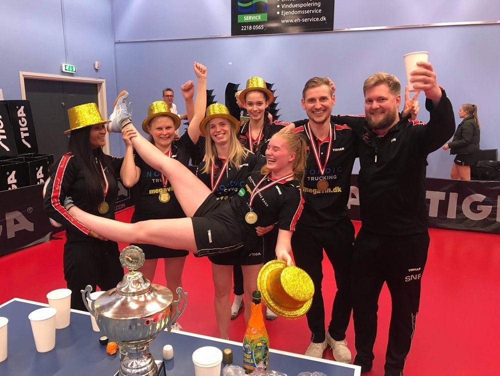 kvindelige bodtennisspillere fejrer et mesterskab med guldhaTTE OG