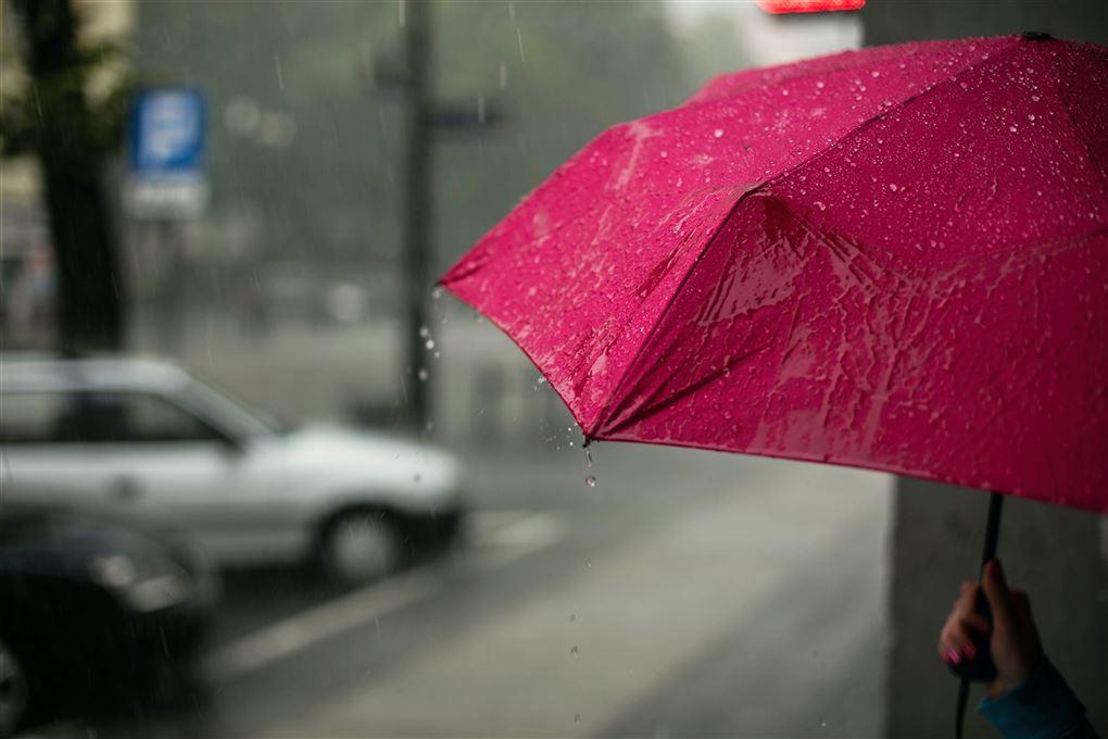 En rød paraply på en gade i regnvejr.