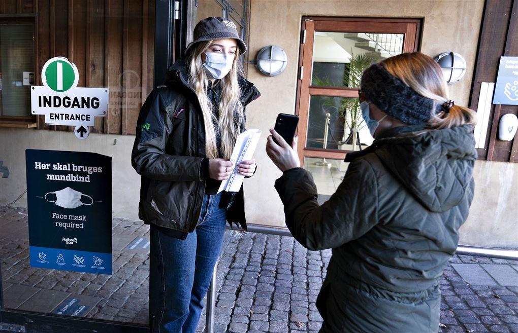 En kvinde med mundbind tjekker en anden kvinde, der også bærer mundbind, for coronapas.