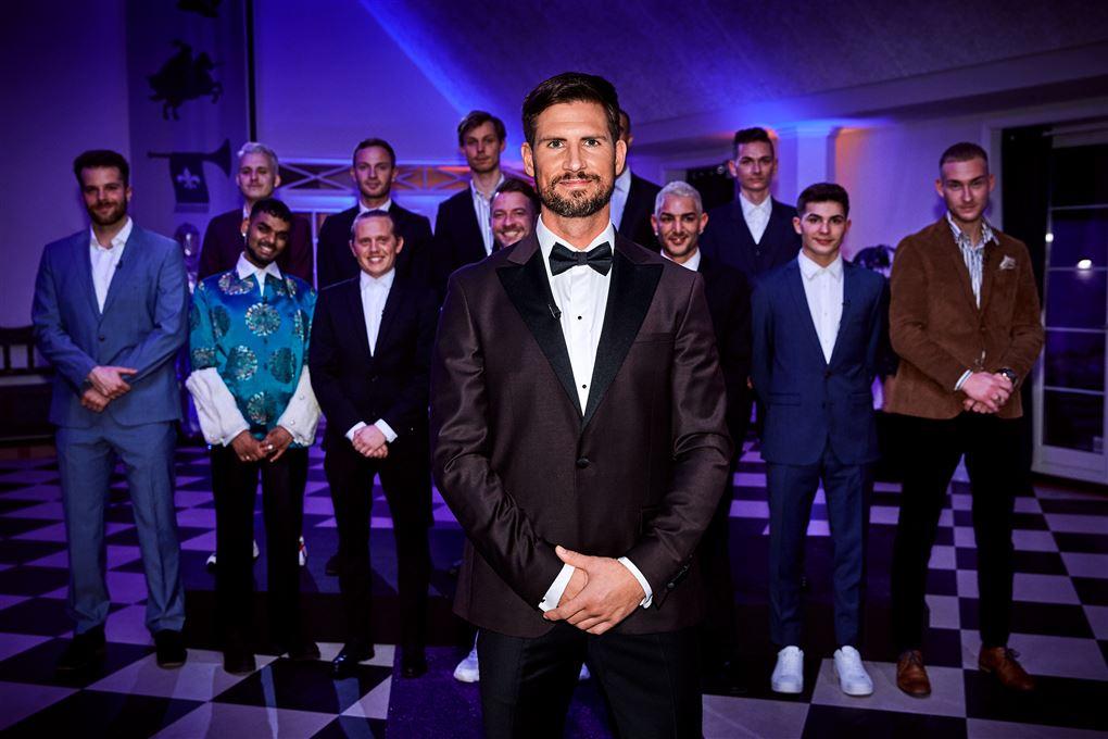 Programmets hovedperson Jonas Løvik med alle sine 12 bejlere i baggrunden.