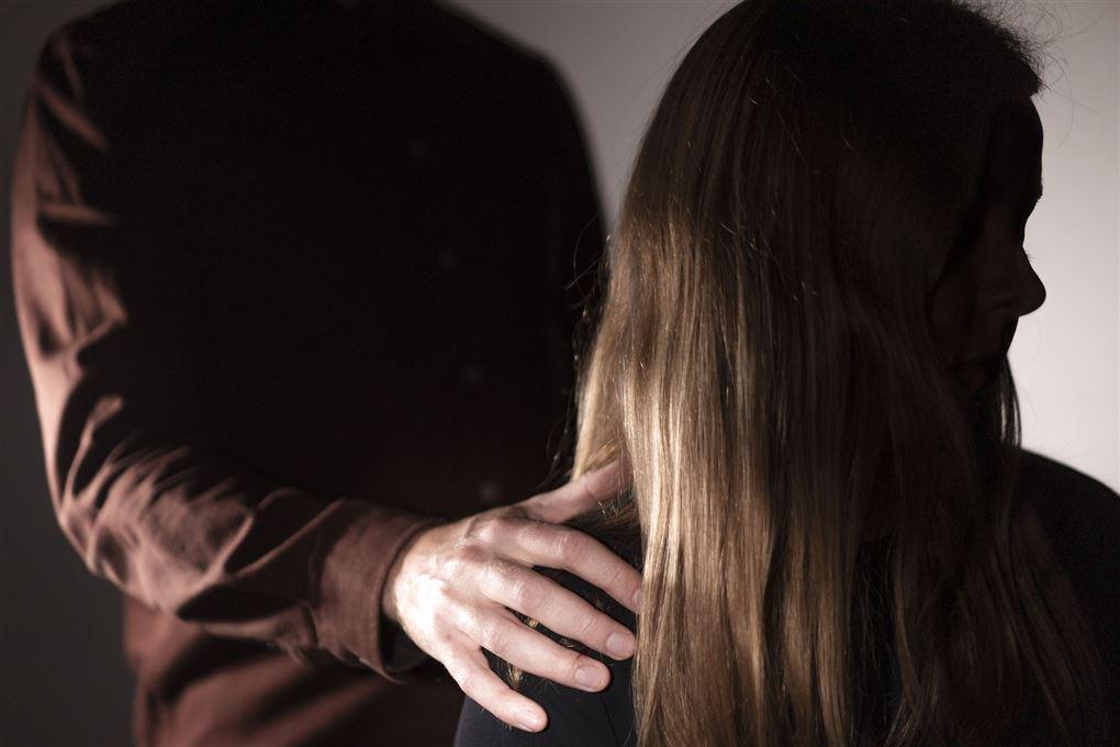 En pige med langhår med siden til, mens en voksen mand står bagved og  holder en hånd på hendes skulder.