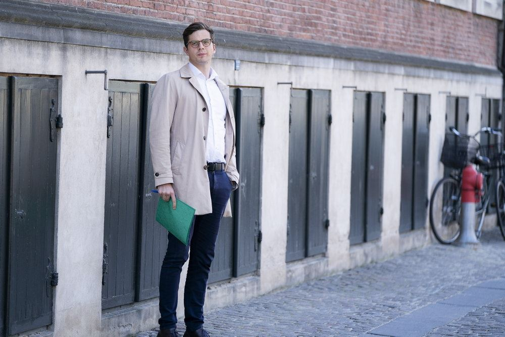 En mand med briller foran nogle garager
