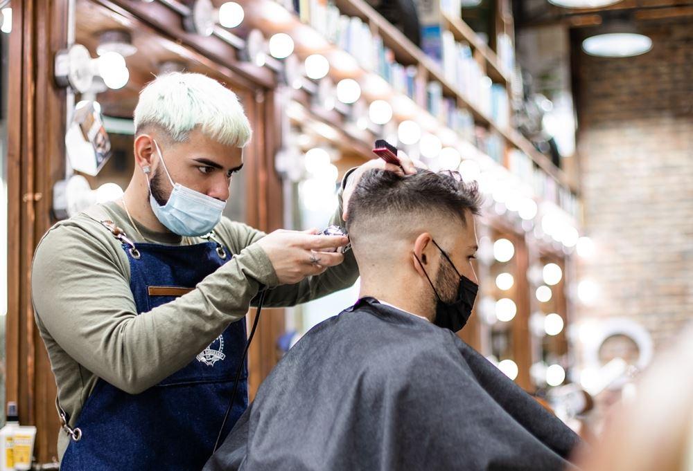 mand bliver klippet af mandlig frisør med mundbind